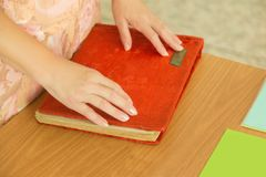 Η γυναίκα έβαλε τα χέρια της στην κόκκινη κάλυψη ενός βιβλίου ή ενός λευκώματος φωτογραφιών, στο γραφείο r στοκ φωτογραφίες με δικαίωμα ελεύθερης χρήσης