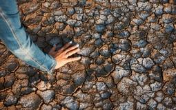 Η γυναίκα έβαλε το χέρι της στο ξηρό ραγισμένο χώμα Στοκ Φωτογραφία