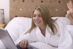 Η γυναίκα έβαλε στο κρεβάτι χρησιμοποιώντας το lap-top Στοκ φωτογραφία με δικαίωμα ελεύθερης χρήσης