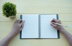 Η γυναίκα έγραψε το βιβλίο με ένα βιβλίο αργίλου σε ένα κίτρινο υπόβαθρο Η τοπ όψη στοκ φωτογραφίες με δικαίωμα ελεύθερης χρήσης