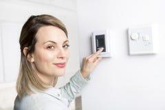 Η γυναίκα έθεσε τη θερμοστάτη στο σπίτι στοκ εικόνες