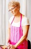 Η γυναίκα έκοψε το κόκκινο κρεμμύδι στον τέμνοντα πίνακα Στοκ φωτογραφία με δικαίωμα ελεύθερης χρήσης