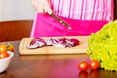 Η γυναίκα έκοψε το κόκκινο κρεμμύδι στον τέμνοντα πίνακα Στοκ Εικόνα