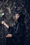 Η γυναίκα έντυσε ως μάγισσα νεράιδων στο αδιάβροχο και με τα κέρατα Στοκ Εικόνες