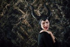 Η γυναίκα έντυσε ως μάγισσα νεράιδων στο αδιάβροχο και με τα κέρατα Στοκ εικόνα με δικαίωμα ελεύθερης χρήσης