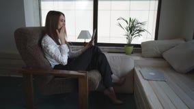 Η γυναίκα έχει την τηλεοπτική κλήση στην ταμπλέτα οθόνης αφής στο σπίτι φιλμ μικρού μήκους