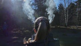 Η γυναίκα έχει τον καπνό που βγαίνει από το κεφάλι και τα αυτιά της Πίσω από το κορίτσι είναι τελετουργικό ashtray δοχείων για υπ απόθεμα βίντεο