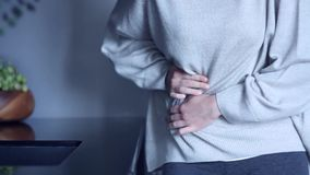 Η γυναίκα έχει τον πόνο στομαχιών στην κουζίνα φιλμ μικρού μήκους