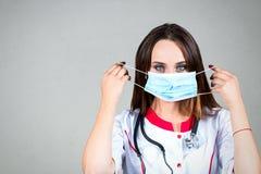 Η γυναίκα ή η νοσοκόμα ή ο γιατρός κοριτσιών στην ιατρική εσθήτα φορούν το προστατευτικό γ Στοκ Φωτογραφίες