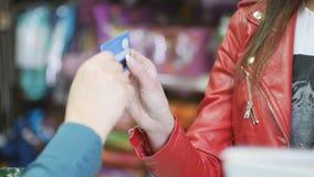 Η γυναίκα δίνει μια πιστωτική κάρτα στον πωλητή στην αγορά φιλμ μικρού μήκους