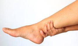Η γυναίκα δίνει το μασάζ ποδιών για την ανακούφιση πόνου Στοκ Εικόνες