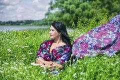 Η γυναίκα αγάπης φύσης στον τομέα λουλουδιών έντυσε στο ζωηρόχρωμο ύφασμα στοκ εικόνα