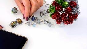 Η γυναίκα αγγίζει το κόσμημα φιαγμένο από πολύτιμο και βασικά μέταλλα, γυαλί, και smartphone φιλμ μικρού μήκους