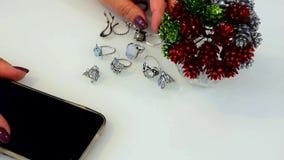 Η γυναίκα αγγίζει το κόσμημα φιαγμένο από πολύτιμο και βασικά μέταλλα, γυαλί, διακοσμητικές πέτρες, Topaz και moonstone, smartpho φιλμ μικρού μήκους