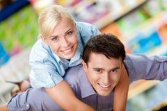 Η γυναίκα αγκαλιάζει τον άνδρα στο κατάστημα στοκ φωτογραφίες