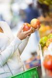 Η γυναίκα αγοράζει τα φρούτα και λαχανικά σε μια αγορά Στοκ Φωτογραφία