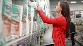 Η γυναίκα αγοράζει τις πάνες στην υπεραγορά, νέες αγορές μητέρων mom απόθεμα βίντεο