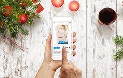 Η γυναίκα αγοράζει τον άλτη με το έξυπνο τηλέφωνο κατά τη διάρκεια του χρόνου Χριστουγέννων Στοκ Φωτογραφία