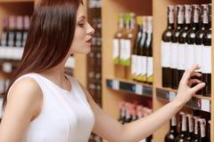 Η γυναίκα αγοράζει το κρασί σε ένα κατάστημα στοκ εικόνα