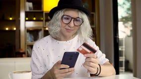 Η γυναίκα αγοράζει το νέο smartphone χρησιμοποίησης φορεμάτων σε απευθείας σύνδεση και την πιστωτική κάρτα απόθεμα βίντεο