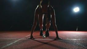 Η γυναίκα αθλητών στα μαύρα σορτς και μια μπλούζα στα πάνινα παπούτσια είναι στα τρέχοντας μαξιλάρια στη διαδρομή του αθλητισμού  φιλμ μικρού μήκους