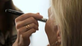 Η γυναίκα αιθουσών ομορφιάς παίρνει concealer το ξανθό δέρμα βουρτσών απόθεμα βίντεο