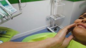 Η γυναίκα αισθάνεται τον πονόδοντο, που περιμένει το γιατρό στην καρέκλα οδοντιάτρων, reliever πόνου απόθεμα βίντεο