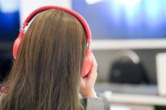 Η γυναίκα ακούει μουσική με την κόκκινη κάσκα της στοκ φωτογραφίες