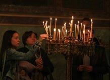Η γυναίκα ανάβει ένα κερί Στοκ εικόνα με δικαίωμα ελεύθερης χρήσης