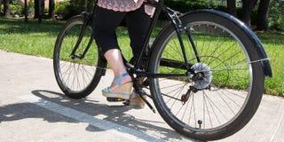 Η γυναίκα ανακυκλώνει στο πάρκο με ένα μαύρο ποδήλατο παραλιών Στοκ Εικόνες