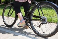Η γυναίκα ανακυκλώνει στο πάρκο με ένα μαύρο ποδήλατο παραλιών Στοκ εικόνες με δικαίωμα ελεύθερης χρήσης