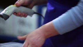 Η γυναίκα ανιχνεύει τους κώδικες φραγμών στις συσκευασίες απόθεμα βίντεο
