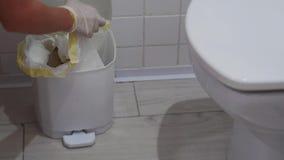 Η γυναίκα ανοίγει ένα άσπρο δοχείο απορριμάτων και παίρνει έξω την τσάντα με τα απορρίμματα φιλμ μικρού μήκους