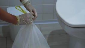 Η γυναίκα ανοίγει ένα άσπρο δοχείο απορριμάτων και παίρνει έξω την τσάντα με τα απορρίμματα απόθεμα βίντεο