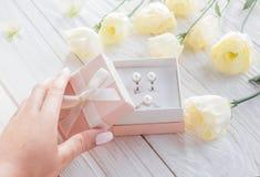 Η γυναίκα ανοίγει ένα κιβώτιο δώρων με τα κοσμήματα Στοκ Εικόνες