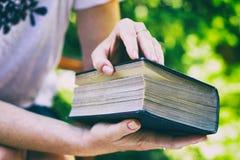 Η γυναίκα ανοίγει ένα μεγάλο παλαιό βιβλίο Στοκ εικόνα με δικαίωμα ελεύθερης χρήσης