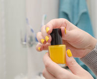 Η γυναίκα ανοίγει μια κίτρινη στιλβωτική ουσία καρφιών Στοκ φωτογραφία με δικαίωμα ελεύθερης χρήσης