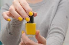 Η γυναίκα ανοίγει μια κίτρινη στιλβωτική ουσία καρφιών Στοκ φωτογραφίες με δικαίωμα ελεύθερης χρήσης