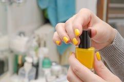 Η γυναίκα ανοίγει μια κίτρινη στιλβωτική ουσία καρφιών Στοκ Φωτογραφία