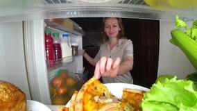 Η γυναίκα ανοίγει το ψυγείο τη νύχτα Πείνα νύχτας διατροφή gluttony στοκ εικόνα