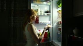 Η γυναίκα ανοίγει το ψυγείο τη νύχτα Πείνα νύχτας σιτηρέσιο κατανάλωση κέικ απόθεμα βίντεο