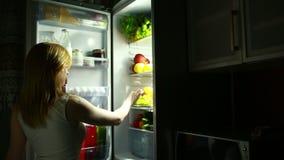 Η γυναίκα ανοίγει το ψυγείο τη νύχτα Πείνα νύχτας σιτηρέσιο Κατανάλωση των σταφυλιών απόθεμα βίντεο