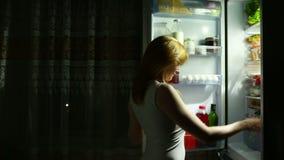 Η γυναίκα ανοίγει το ψυγείο τη νύχτα Πείνα νύχτας σιτηρέσιο gluttony απόθεμα βίντεο