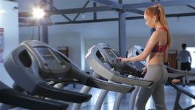 Η γυναίκα ανοίγει treadmill στο κέντρο ικανότητας φιλμ μικρού μήκους