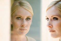 η γυναίκα αντανάκλασής τη&sig Στοκ φωτογραφία με δικαίωμα ελεύθερης χρήσης