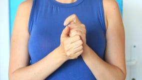 Η γυναίκα αποβουτυρώνει τα χέρια της για το μαλακό skincare Μια γυναίκα λερώνει τα χέρια της με μια κρέμα χεριών στο υπόβαθρο της απόθεμα βίντεο