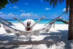 Η γυναίκα απολαμβάνει τη θέα σε μια τροπική παραλία στις Μαλδίβες στοκ εικόνες