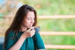Η γυναίκα απολαμβάνει το νόστιμο καφέ που έχει το πρόγευμα στον υπαίθριο καφέ Ευτυχής νέος αστικός καφές κατανάλωσης γυναικών Στοκ Εικόνες