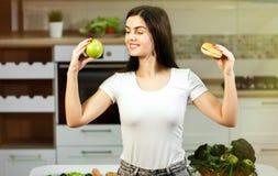 Η γυναίκα αποφασίζει μεταξύ της Apple και του χάμπουργκερ Στοκ Φωτογραφία