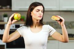 Η γυναίκα αποφασίζει μεταξύ της Apple και του χάμπουργκερ Στοκ Εικόνες